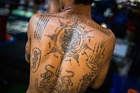 Traditional Thai tattoos, some of them thought to be akin to protective amulets, adorn the back of a young Muay Thai fighter in Bangkok, Thailand.