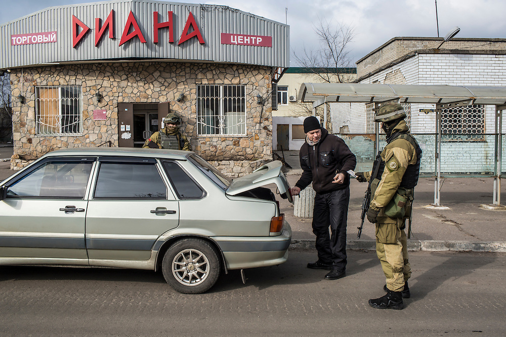 MARIINKA, UKRAINE - FEBRUARY 21, 2016: Ukrainian soldiers search vehicles at an intersection in the front-line town of Mariinka, Ukraine. The Donetsk suburb has been the scene of some of the heaviest fighting recently between Ukrainian forces and pro-Russian rebels. CREDIT: Brendan Hoffman for The New York Times