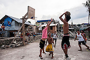 Kids play basketball surrounded by the ruins of magallanes neighbourhood on June 11 2014 in Tacloban, Philippines. Tacloban city and the surrounding villages were devastated after typhoon Hayan passed over leaving at least 6,200 people dead and a high number of disappeared on November 8, 2013.