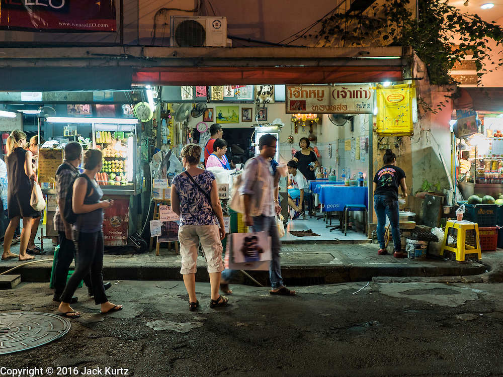17 JANUARY 2016 - BANGKOK, THAILAND:  Tourists walk along Sukhumvit Soi 38, one of the most famous street food areas in Bangkok. The food carts and small restaurants along the street have been popular with tourists and Thais alike for more than 40 years. The family that owns the land along the soi recently decided to sell to a condominium developer and not renew the restaurant owners' leases. More than 40 restaurants and food carts will have to close. Most of the restaurants on the street closed during the summer of 2015. The remaining restaurants are supposed to close by the end of this week.      PHOTO BY JACK KURTZ