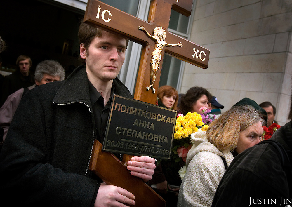 A man holds a cross at the funeral of Russian journalist Anna Politkovskaya, murdered in Moscow on 7 October, 2006. She was shot four times, once in the head, in an elevator in her apartment block. .The funeral, held in the Troyekurovskoye cemetery in western Moscow, was conducted by an Orthodox priest. Before the burial, thousands of well-wishers filed passed her body..Known for her critical coverage of the war in Chechnya and of Russian President Vladimir Putin, her murder is widely believed to be connected to her investigative work..The 48-year-old was a tireless reporter who had written a critical book on Russian President Vladimir Putin and his campaign in Chechnya, documenting widespread abuse of civilians by government troops..She leaves behind a son, a daughter and an ex-husband.