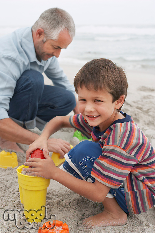 Father and son (5-6) playing in sand on beach