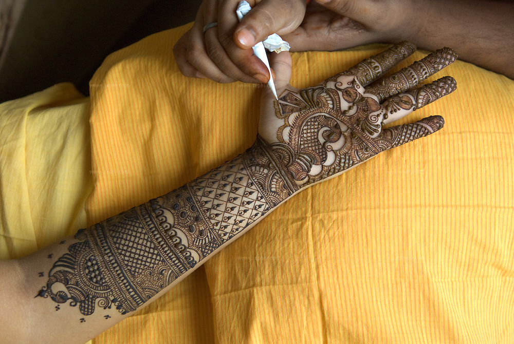 during the Mehendi day professional henna artists are hired to painstakingly work out the intricate details and beautiful designs on the bride's hands and feet