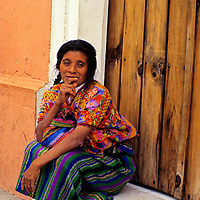 Central America, Guatemala, Antigua. A colorfully dressed Guatemalan woman sits lost in  thought on her doorstep in Antigua, Guatemala.