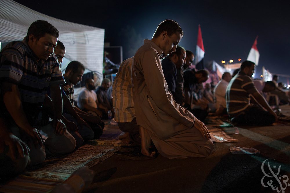 Supporters of deposed Egyptian president Mohamed Morsi say a prayer for the dead as they mourn the death of at least 65 fellow protestors slain during overnight clashes at the edge of the continuing large scale sit-in around the Rabaah al-Adawia square in the Nasr City district of Cairo Friday July 28, 2013.  In addition to the 65 killed, another 61 are on life support according to the Muslim Brotherhood and 3000 injured by tear gas fired by authorities.