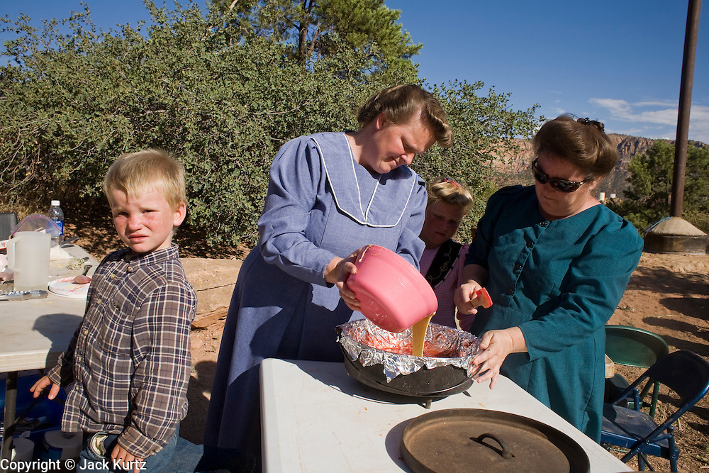 """Aug 9, 2008 -- COLORADO CITY, AZ: Members of the Jessop family make fruit cobbler during a family picnic near the family's home in Colorado City, AZ. Colorado City and neighboring town of Hildale, UT, are home to the Fundamentalist Church of Jesus Christ of Latter Day Saints (FLDS) which split from the mainstream Church of Jesus Christ of Latter Day Saints (Mormons) after the Mormons banned plural marriage (polygamy) in 1890 so that Utah could gain statehood into the United States. The FLDS Prophet (leader), Warren Jeffs, has been convicted in Utah of """"rape as an accomplice"""" for arranging the marriage of teenage girl to her cousin and is currently on trial for similar, those less serious, charges in Arizona. After Texas child protection authorities raided the Yearning for Zion Ranch, (the FLDS compound in Eldorado, TX) many members of the FLDS community in Colorado City/Hildale fear either Arizona or Utah authorities could raid their homes in the same way. Older members of the community still remember the Short Creek Raid of 1953 when Arizona authorities using National Guard troops, raided the community, arresting the men and placing women and children in """"protective"""" custody. After two years in foster care, the women and children returned to their homes. After the raid, the FLDS Church eliminated any connection to the """"Short Creek raid"""" by renaming their town Colorado City in Arizona and Hildale in Utah. A member of the Jessop family weeds the community corn plot in Colorado City, AZ. The Jessops are a polygamous family and members of the FLDS. Photo by Jack Kurtz / ZUMA Press"""
