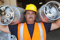 Portrait of a middle-aged man carrying cylinders