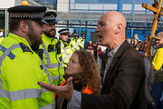 Environmental activists argue with police officers while protesting about Climate Change during the occupation of City Airport (London's Business Travel hub) in east London, the fourth day of a two-week prolonged worldwide protest by members of Extinction Rebellion, on 10th October 2019, in London, England.