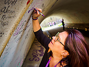 21 APRIL 2017 - CHANHASSEN, MN: AMY AUSTIN, from Naples, FL, writes a note to Prince in the pedestrian tunnel in front of Paisley Park, his former home and recording studio. The tunnel has become a memorial to Prince, people have drawn graffiti in the tunnel honoring him and they leave memorials in the tunnel. The superstar died from an accidental overdose of the opioid fentanyl on April 21, 2016. Friday was the first anniversary of his death. Crowds of people gathered at Paisley Park, which is now a museum, to honor the Minnesota born musician.     PHOTO BY JACK KURTZ