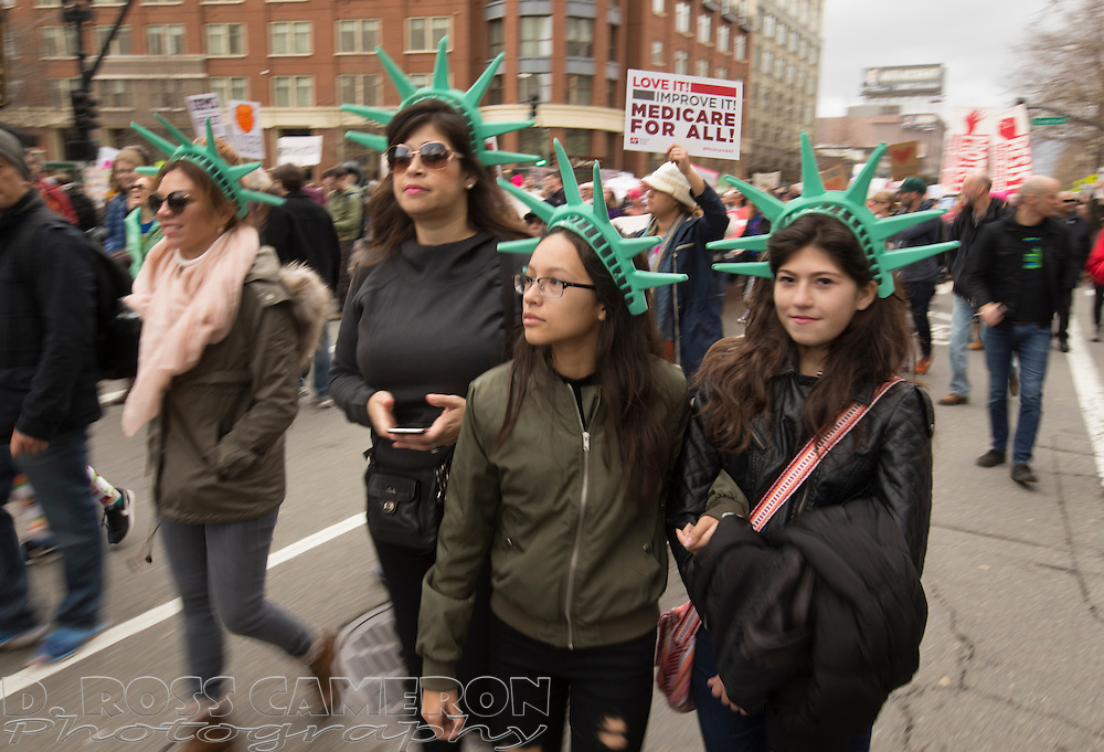 Four women wearing Statue of Liberty crowns join other demonstrators as they march through the streets of Oakland, Calif., Saturday, Jan. 21, 2017, to protest against the curtailment of women's rights and civil rights proposed by Pres. Donald J. Trump. An estimated 60,000 people attended the event, one of hundreds that occurred around the world. (Photo by D. Ross Cameron)
