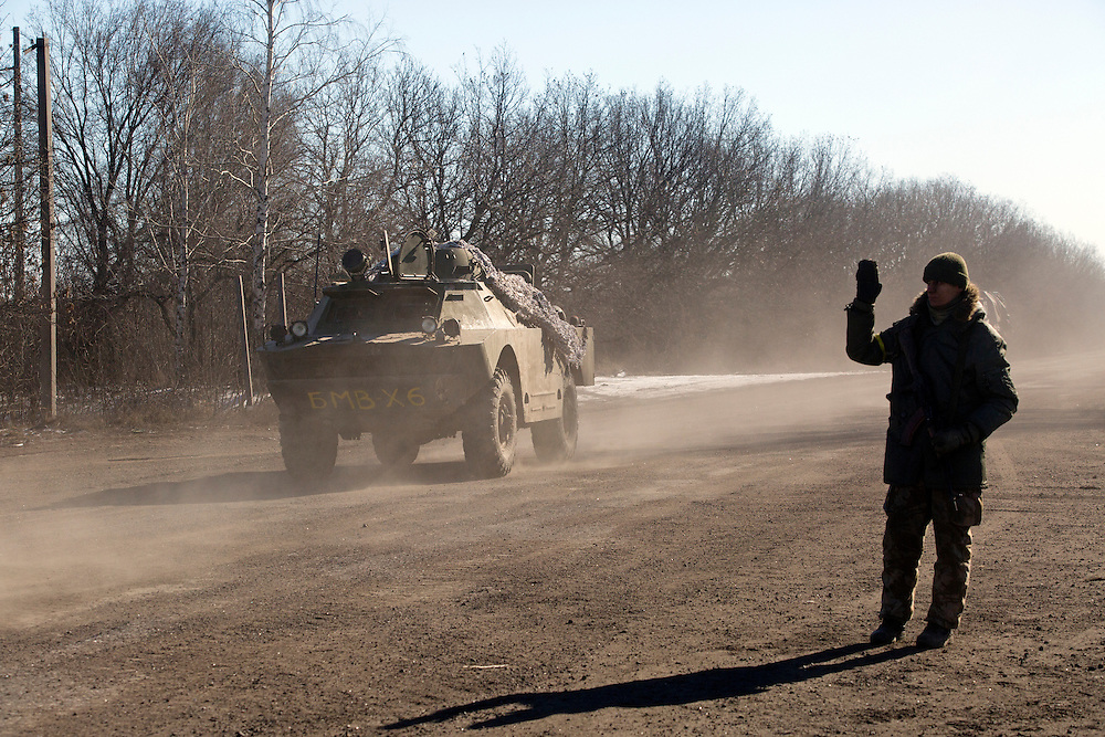A soldier manning a checkpoint waves as vehicles drive away from Debaltseve, Ukraine on February 18, 2015 on a road about 30 kilometers from the city. Wednesday saw a steady stream of vehicles leaving the embattled city, which had apparently fallen to separatist forces.