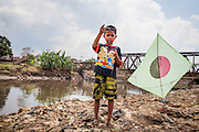A boy flies his kite on the bank of the Citarum River. Citeureup Village, Kabupaten Bandung...Credit: Andri Tambunan for Greenpeace