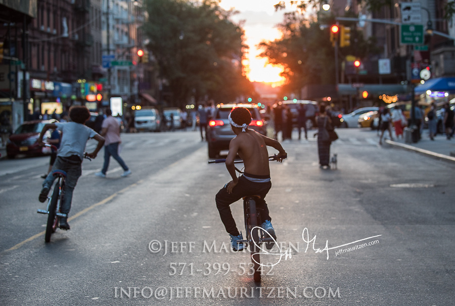 Kids ride bikes and people stand in the street watching Manhattanhenge in New York City.