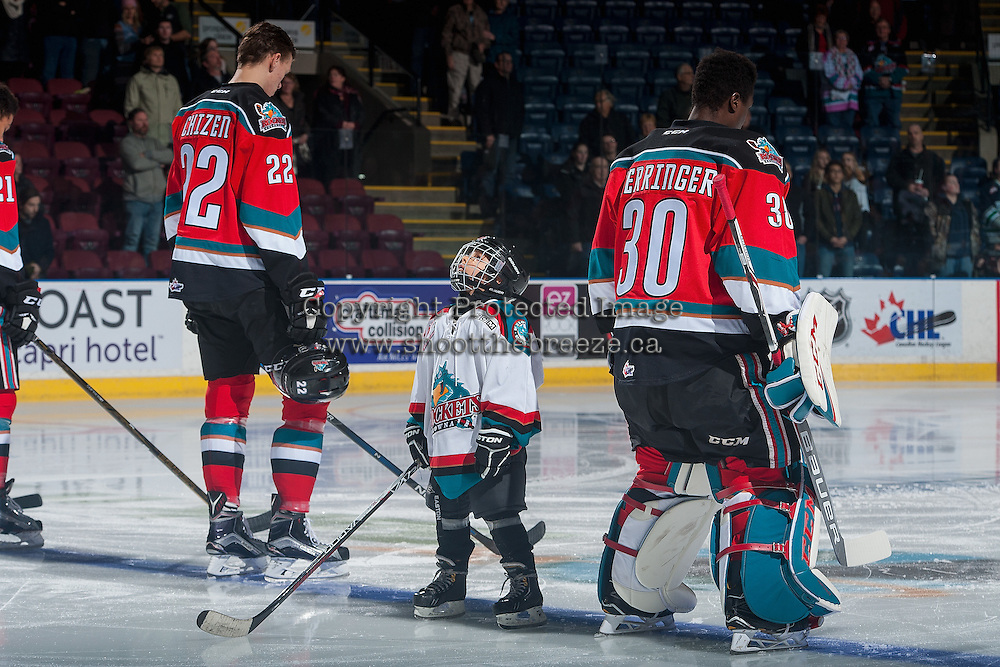 KELOWNA, CANADA - DECEMBER 7: The Pepsi Player of the game watches the jumbotron between Braydyn Chizen #22 and Michael Herringer #30 of the Kelowna Rockets during the national anthem on December 7, 2016 at Prospera Place in Kelowna, British Columbia, Canada.  (Photo by Marissa Baecker/Shoot the Breeze)  *** Local Caption ***