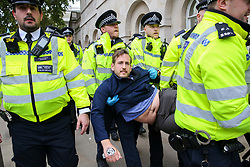 © Licensed to London News Pictures. 07/10/2019. London, UK. Police officers detain environmental and climate change activist from the Extinction Rebellion movement outside Downing Street as campaigners call for the UK Government to take responsibility and enact immediate, profound and sweeping changes to address the crisis on climate and ecological changes. Photo credit: Dinendra Haria/LNP