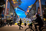 """People walk and cycyle past """"The Place"""", a new open-air shopping mall with the biggest LCD screen in Asia as its roof."""