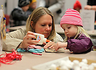 Roxann Osterman (from left) and Autumn Osterman, 3, of Marion, work on making a Christmas tree ornament at the Marion Public LIbrary during Christmas in the Park and Peppermint Walk on Friday evening, December 2, 2011. (Stephen Mally/Freelance)