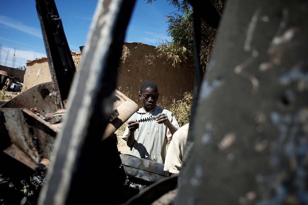 January 21, 2013 - Diabaly, Mali: Local children scavenge destroyed islamic militants' armoured vehicles in central Diabaly, a day after Mali government troops regain control of the city. Diabaly was under islamist militants control since the 14th of January.<br /> <br /> Several insurgent groups have been fighting a campaign against the Malian government for independence or greater autonomy for northern Mali, an area known as Azawad. The National Movement for the Liberation of Azawad (MNLA), an organisation fighting to make Azawad an independent homeland for the Tuareg people, had taken control of the region by April 2012.<br /> <br /> The Malian government pledge to the French army to help the national troops to stop the rebellion advance towards the capital Bamako. The french troops started aerial attacks on rebel positions in the centre of the country and deployed several hundred special forces men to counter attack the advance on the ground. (Paulo Nunes dos Santos/Polaris)
