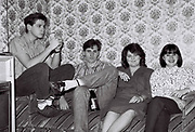 Group of four friends sitting on rented house sofa, London, UK, 1985.