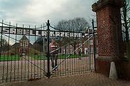 Nederland, Vught , 20030125. AMA Campus in Den Bosch. <br /> Jongen staat achter het hek van de campus. <br /> <br /> Het asielzoekerscentrum in de voormalige Isabella-kazerne in Vught is in september 2002 omgebouwd tot de eerste Nederlandse campus voor alleenstaande minderjarige asielzoekers (ama's). In het centrum moeten jongeren tussen 15 en 17 jaar worden voorbereid op een terugkeer naar hun moederland. <br /> Het is een  experiment, dat een jaar gaat duren. De ama-campus is het gevolg van het strengere beleid dat de vorige staatssecretaris van Justitie, Kalsbeek, voor de ama's in gang heeft gezet. Het Centraal Orgaan opvang Asielzoekers (COA) schotelt hen een strak dagprogramma voor, waarin onderwijs en recreatie de voornaamste elementen zijn. Het is de bedoeling dat zij het terrein niet verlaten, maar het is juridisch onmogelijk om de ama's dat te verbieden.