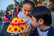 "17 NOVEMBER 2013 - BANGKOK, THAILAND: A mother and her son pray before floating their krathong in the Chao Phraya River at Wat Yannawa on Loy Krathong in Bangkok. Loy Krathong (also written as Loi Krathong) is celebrated annually throughout Thailand and certain parts of Laos and Burma (in Shan State). The name could be translated ""Floating Crown"" or ""Floating Decoration"" and comes from the tradition of making buoyant decorations which are then floated on a river. Loi Krathong takes place on the evening of the full moon of the 12th month in the traditional and they do this all evening on the 12th month Thai lunar calendar. In the western calendar this usually falls in November. The candle venerates the Buddha with light, while the krathong's floating symbolizes letting go of all one's hatred, anger, and defilements       PHOTO BY JACK KURTZ"