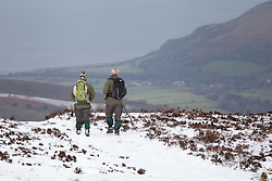 © Licensed to London News Pictures. 14/01/2015. Wheddon Cross, Devon, UK. Two dog walkers on Dunkery Hill in Exmoor National Park, Devon this morning, 14th January 2015. Snow has fallen overnight across many parts of England, causing travel disruption in some areas.  Photo credit : Rob Arnold/LNP