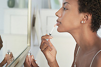 Woman applying lip gloss in mirror close-up