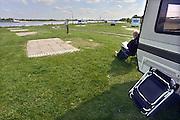 Nederland, Gendt, 3-6-2013Op camping Waalstrand zijn de meeste caravans naar hoger gelegen land verplaatst vanwege het verwachte hoogwater in de Waal.  Een bezoeker is klaar voor vertrek en leest nog wat. Foto: Flip Franssen/Hollandse Hoogte
