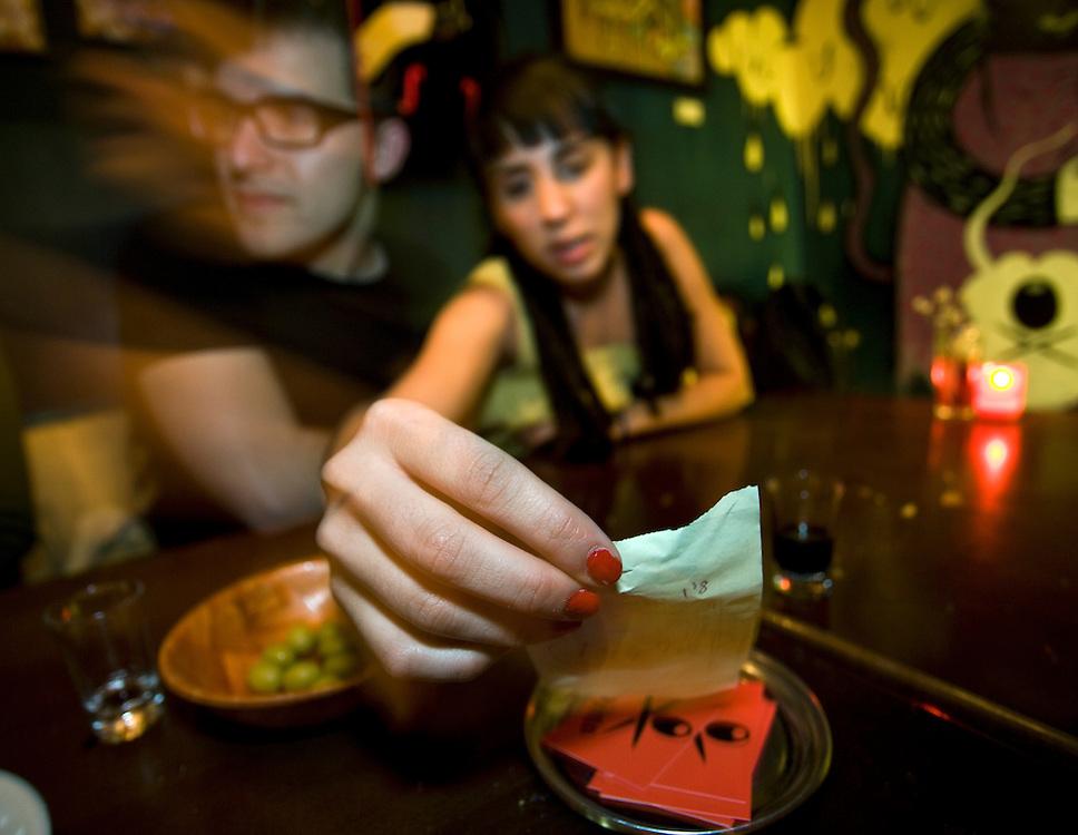 "00:01 AM: Fermín Álvarez, 25, and Ángela Hermosa, 23, check the bill after a tapas dinner at ""Carajillo"", in Madrid.."