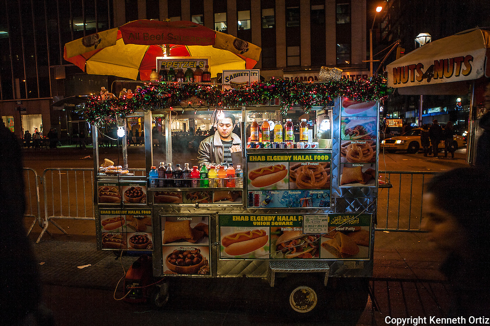 A hot dog vendor on sixth avenue in New York City, prepares his food