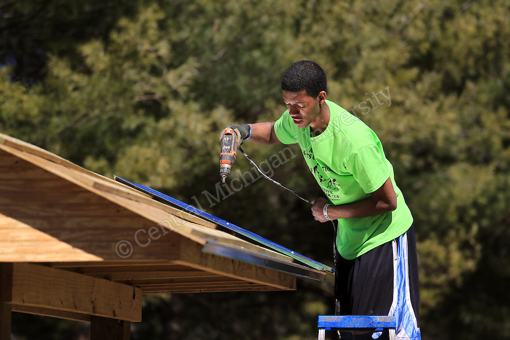 Rajaah Salaam, of Flint, drills holes and hammers nails to attach the metal roof on the garden kiosk they were building. He was among nine CMU students spending their Alternative Break at theYMCA of Western NC Youth Service Center for the week to help with projects to improve the center and in the community. They addressed access to sports and recreation and built a kiosk, cleared a stream bed and worked with elementary students in an after school program as their Alternative Break project. CMU is ranked fourth in the nation for the number of students participating in Alternative Breaks and fifth in the country for the most trips coordinated by a university. The program organizes about 40 trips each year with more than 400 students participating. Photo by Steve Jessmore/Central Michigan University