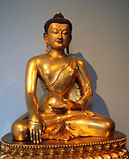 Seated Buddha, Chinese, 1740-1786 is shown just before his enlightenment.  Gilded copper.