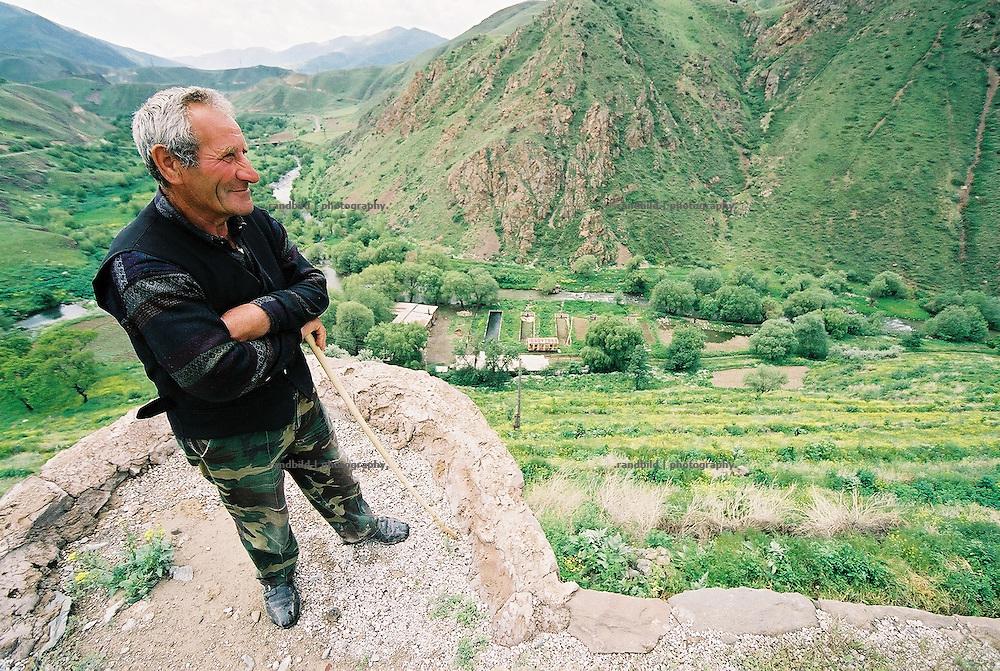 Auf seinen Stock gestützt blickt ein Armenier über ein Tal in der Bergregion um die armenische Stadt Sissian. An armenian man overlooks a deep green valley in rural region.