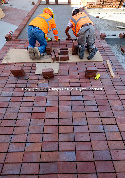 Workers install the bricks in USC's University Village. USC's $700 million shopping and residential complex is nearly complete and more than a dozen retailers (Trader Joe's, Target, Starbucks, etc.) are set to open in August.(Photo by Ringo Chiu)<br /> <br /> Usage Notes: This content is intended for editorial use only. For other uses, additional clearances may be required.
