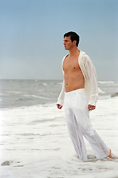 man in wet white clothes standing in the ocean in Montauk, NY