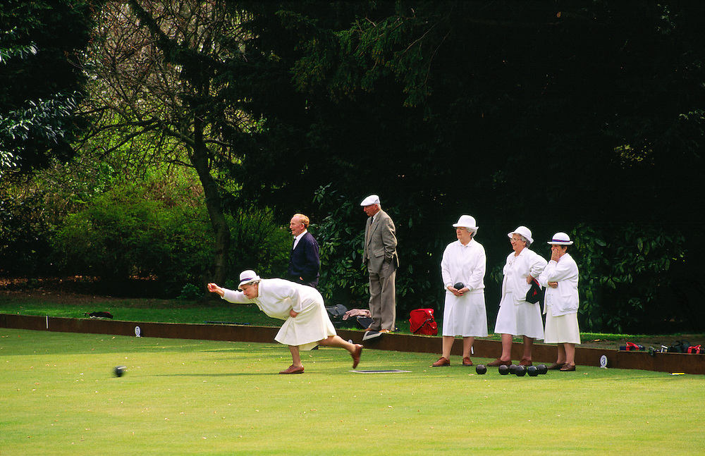 English ladies and gentlemen playing crown green bowling in the town of Barnard Castle, County Durham, England, UK. Summer.
