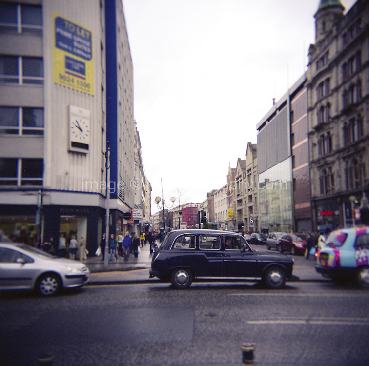 Traditional black taxi cab driving past Donegal Place shopping area in Belfast Northern Ireland