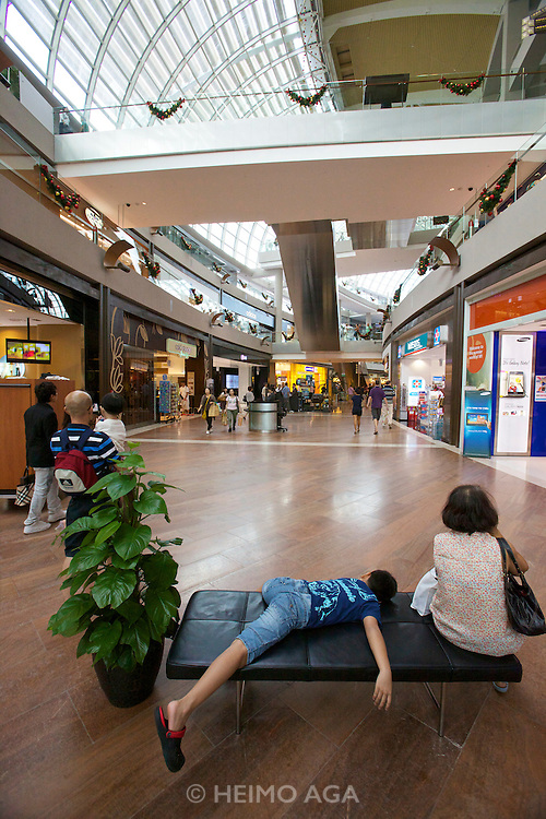 Singapore. Marina Bay Sands. The Shopping Mall. Young visitor relaxing on a bench.