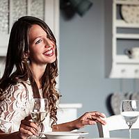 Junge Frau lachend mit Weinglas am Tisch, Möbel im Landhaus-Stil, Starnberger See, München, Bayern, Deutschland