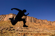 Man in silhouette limbering up before climbing the red rock cliffs of the Big Bend State Park near Moab, UT