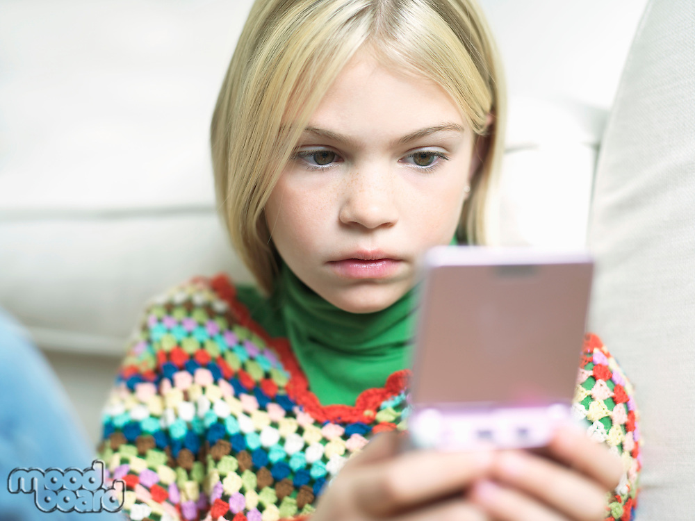 Young Girl concentrating Playing Handheld Video Game