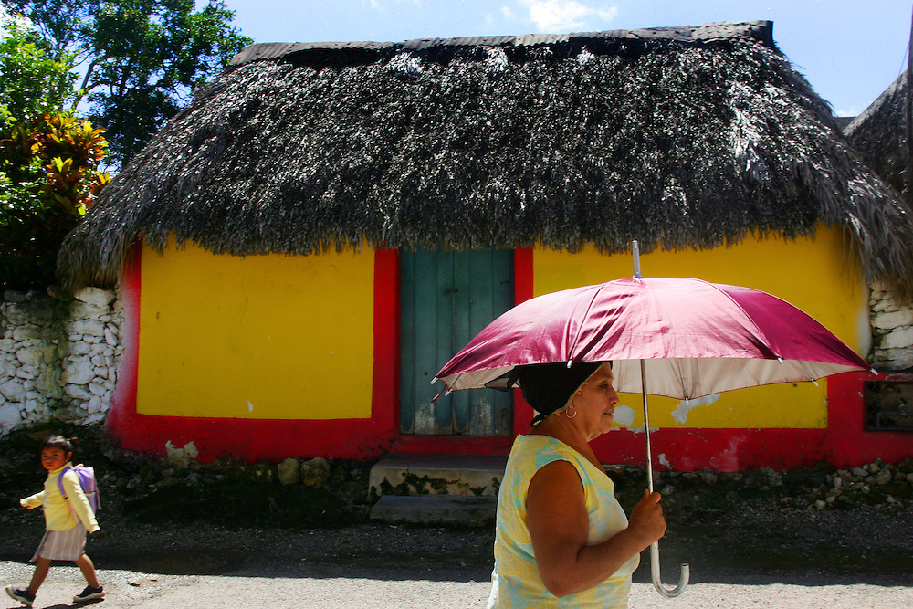 A lady shades herself from the sun as a school girl walks past in the town of Calotmul.