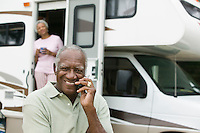 Senior man sitting in front of a caravan