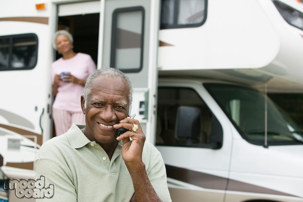Senior man sitting in front of a caravan