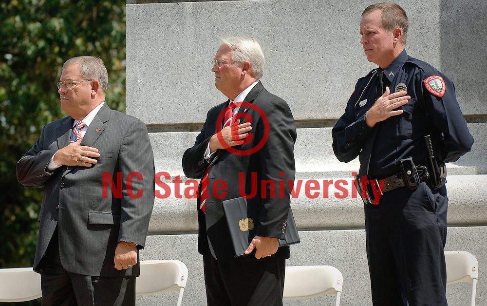 Benny Suggs, left, Chancellor Woodson, center, and NC State Police officer Charlie Corr stand for the singing of the National Anthem.