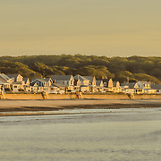 A glorious, sunny morning on Cape Ann in Gloucester, MA.  The tide is starting to come in.  The gulls keep darting along the shore ahead of the waves while the houses along the sea wall bathe in the golden light of dawn.