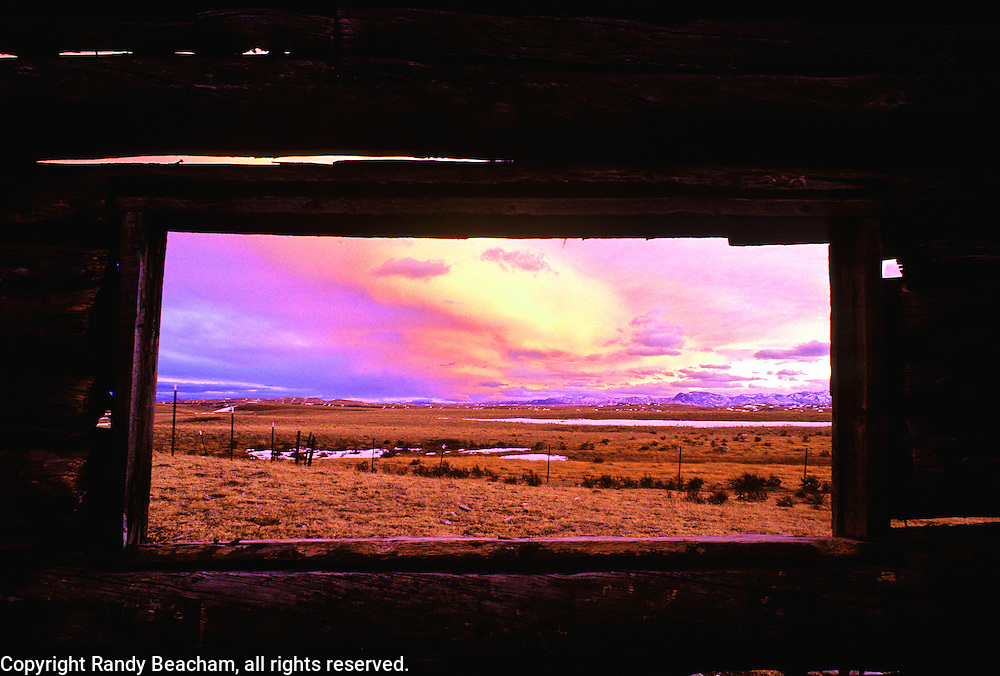 Sunset along the Rocky Mountain Front from inside old log cabin. West of Augusta, Montana.