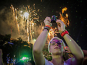 31 DECEMBER 2012 - BANGKOK, THAILAND:  Tourists watch the fireworks show at the New Year's Eve party and countdown in the Ratchaprasong intersection in Bangkok. The traditional Thai New Year is based on the lunar calender and is celebrated in April, but the Gregorian New Year is celebrated throughout the Kingdom, especially in larger cities and tourist centers, like Bangkok, Chiang Mai and Phuket. The Bangkok Countdown 2013 event was called ?Happiness is all Around @ Ratchaprasong.? All of the streets leading to Ratchaprasong Intersection were closed and the malls in the area stayed open throughout the evening.   PHOTO BY JACK KURTZ
