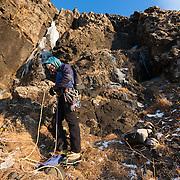 """Freyr Ingi Björnsson at the base of the iceclimb """"Nálaraugað"""" WI4, Búahamrar, Esja."""