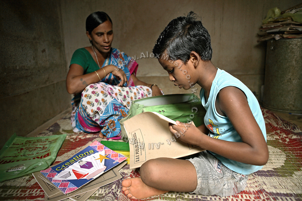 Budhia Singh, (right) 6, the famous Limca World Record marathoner, is preparing to do his homework helped by his mother, Sukanti Singh, 37, (left) in the house where they now live situated inside Salia Sahi slum (pop. 30.000) of Bhubaneswar, the capital of Orissa State, on Friday, May 16, 2008. On May 1, 2006, Budhia completed a record breaking 65 km run from Jagannath temple, Puri to Bhubaneswar. He was accompanied by his coach Biranchi Das and by the Central Reserve Police Force (CRPF). On 8th May 2006, a Government statement had ordered that he stopped running. The announcement came after doctors found the boy had high blood pressure and cardiological stress. As of 13th August 2007 Budhia's coach Biranchi Das was arrested by Indian police on suspicion of torture. Singh has accused his coach of beating him and withholding food. Das says Singh's family are making up charges as a result of a few petty rows. On April 13, Biranchi Das was shot dead in Bhubaneswar, in what is believed to be an event unconnected with Budhia, although the police is investigating the case and has made an arrest, a local goon named Raja Archary, which is now in police custody. **Italy and China Out**